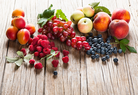 Organic fruits and berries with green leaves  on a rustic wooden background