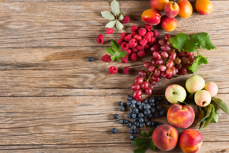 trompo de madera: Group of different fruits and berries  on wooden table with space for text, top view Foto de archivo