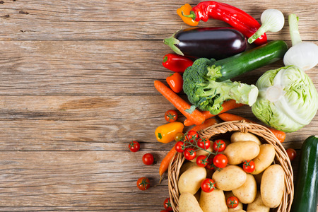 Group of raw vegetables on a rustic wooden background, top view. Copy space for text.