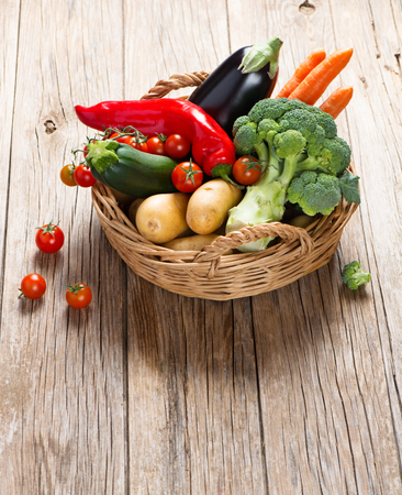 summer fruits: Fresh vegetables in a basket on a rustic wooden table  with space for text. Stock Photo