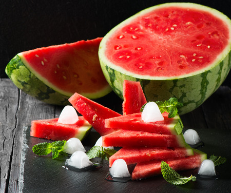 seedless: Seedless ripe watermelon cut slices with mint and ice on a black background