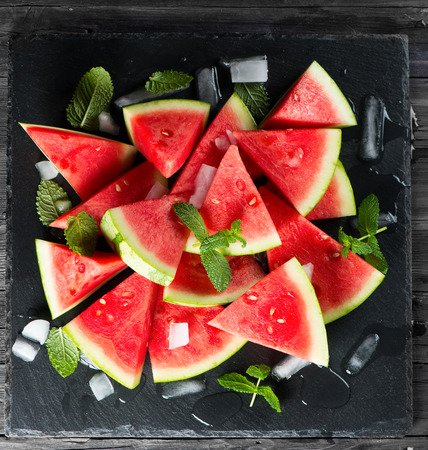 seedless: Organic seedless watermelon cut into wedges with ice and mint  on a slate board over black background, top view Stock Photo