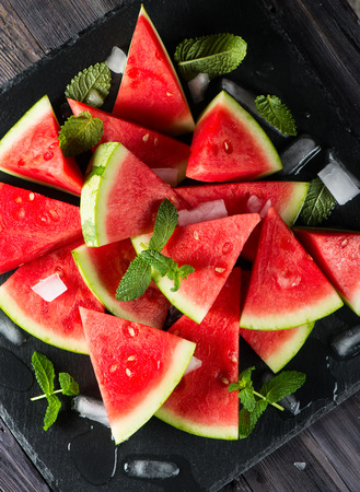 seedless: Sliced seedless watermelon with ice and leaves of mint, top view on a black board
