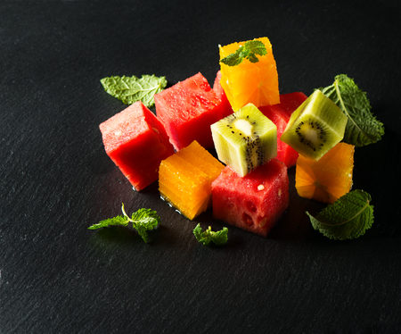 a portion: Fruit salad with watermelon, oranges and kiwi on a black slate board Stock Photo