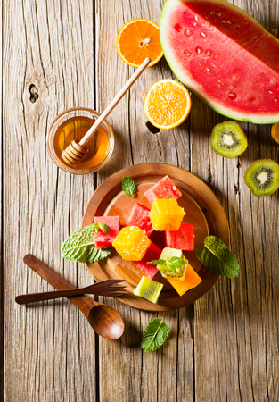ensalada de frutas: Fruit mix salad  and  ingredients on the rustic wooden table, view from above