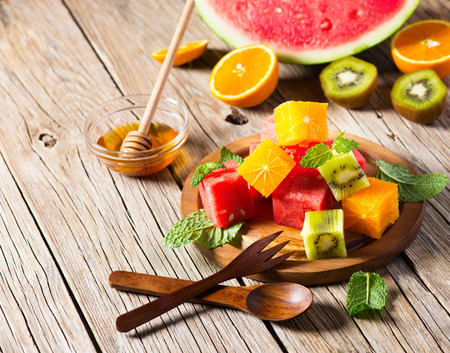 Fresh fruit salad in a wooden plate. Luscious healthy eating, with kiwi fruit,  watermelon, oranges, mint and honey on a rustic background