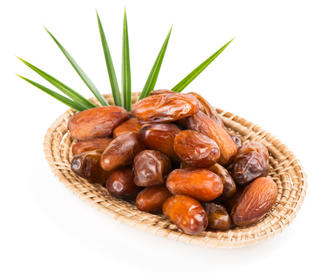 palm fruits: Date fruits in a wicker plate with green leaf of palm,  isolated on white background, selective focus