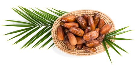 palm fruits: Top view of dried date fruits in a wicker plate on a big leaf of palm tree isolated on white