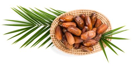 frutas deshidratadas: Vista superior de fecha frutos secos en un plato de mimbre en una gran hoja de palmera aislado en blanco