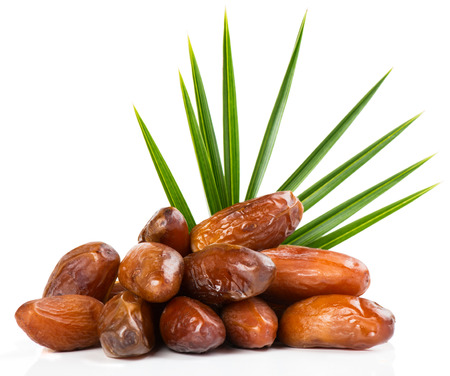 Pile of dried date fruits with green leaf of palm isolated on white background