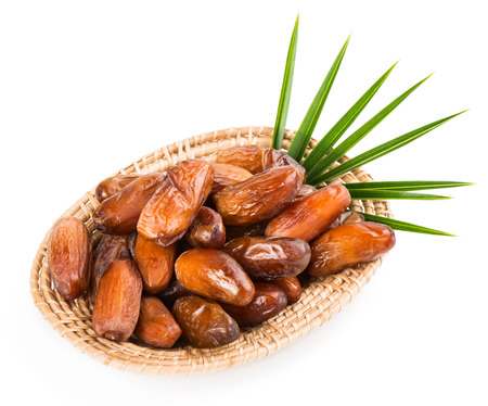 palm fruits: Date fruits in a wicker plate with green leaf of palm tree isolated on white background