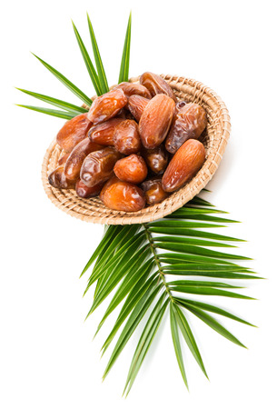 palm fruits: Dried date fruits in a wicker tray on a big leaf of palm tree isolated on white background, selective focus Stock Photo