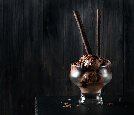 Chocoladeroomijs met wafeltokken met decoratieve chocoladeschilfers en saus op een zwarte achtergrond met ruimte voor tekst Stockfoto