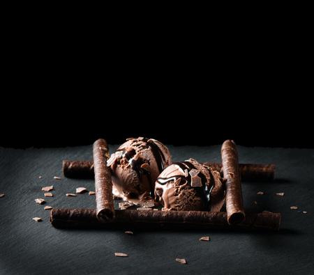 postres: Bolas de helado de chocolate sobre fondo negro con espacio para texto Foto de archivo