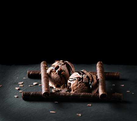 Scoops of chocolate ice cream on black background with space for text