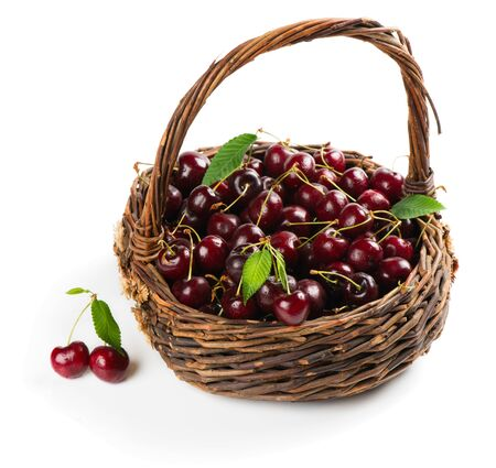 cereza: Old basket full of fresh red cherry with green leaves on a white background Foto de archivo