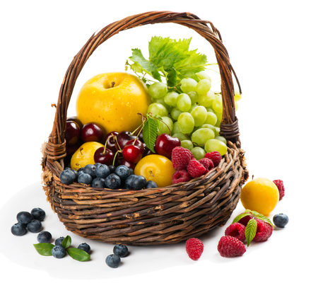 fruits in a basket: Old basket full of fresh different fruits and berries  with green leaves on a white background