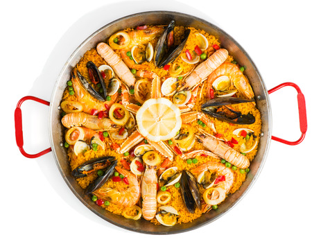 spanish food: Top view of typical spanish seafood paella in traditional pan isolated on white background Stock Photo