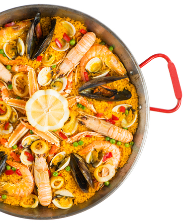 Spanish dish paella with seafood in traditional pan, view from above.  Isolated on a white background.