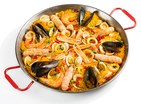 Paella with seafood in a paellera isolated on white background