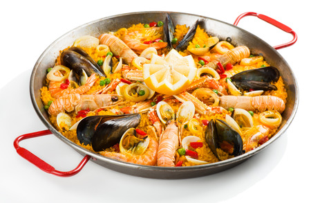 Typical spanish seafood paella in traditional pan isolated on white background