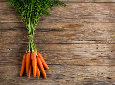 Bunch of fresh carrot on wooden background, with space for text, top view