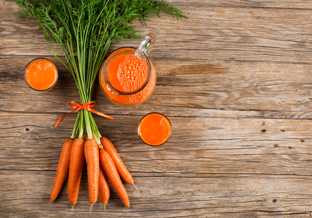 carrot juice: Glasses and jug of carrot juice and fresh carrots on old wooden background with space for text, top view.