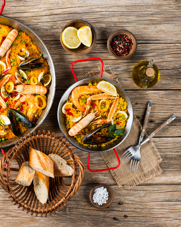 Seafood paella in a paella pans on a rustic wooden background, shot from above Stock Photo