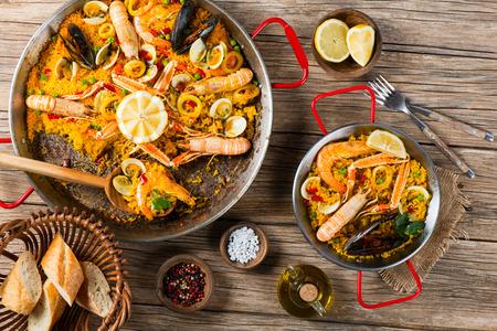 Bovenaanzicht van paella met garnalen, mosselen en citroen, houten achtergrond Stockfoto
