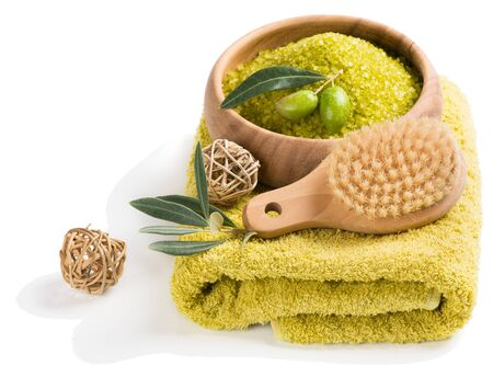 spa therapy: Spa theme. Bowl of bath sea salt, brush, towel and twig of olive tree isolated on white