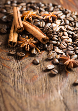 large bean: Coffee beans, cinnamon sticks and stars anise on old wooden background with copy space for text