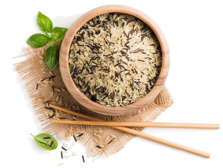 야생 쌀과 나무 그릇에 흰 쌀의 상위 뷰 흰색 배경에 고립입니다. 스톡 콘텐츠