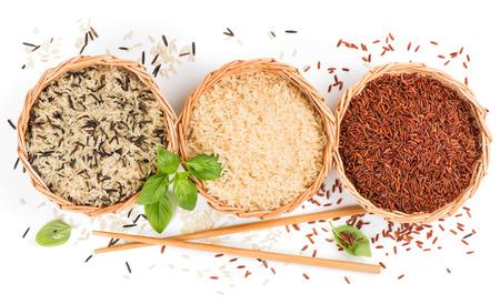 Hoogste mening van verschillende rijsttypes in manden die met basilicum en eetstokjes worden verfraaid die op witte achtergrond worden geïsoleerd Stockfoto