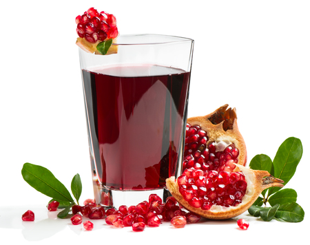 Pomegranate juice in a glass and ripe pomegranate. Isolated on white background