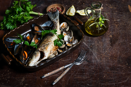 cooked fish: Delicious seabass baked with mussels served with parsley, lemon and olive oil on a wooden old table