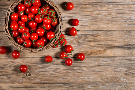 food basket: Top view of Wicker basket with cherry tomatoes on a rustic wooden background  with copy space Stock Photo