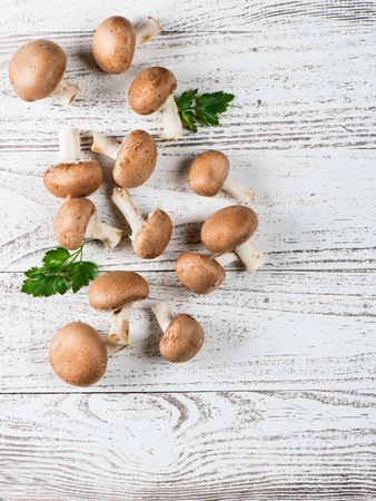 champignon: Champignons mushroom with parsley on a vintage white wooden background, view from above Stock Photo