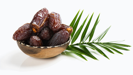 Dried date palm tree fruits and green leaf isolated on white Stock Photo
