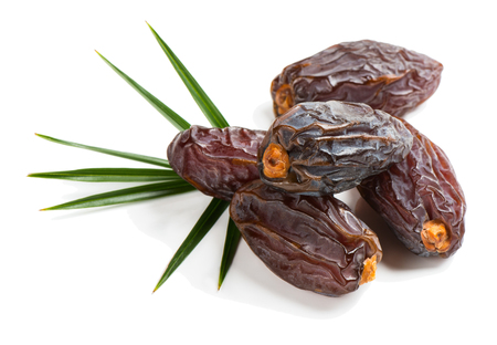 up to date: Close up view of some medjool date fruits with green leaf isolated on white background