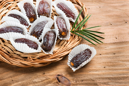 date palm tree: Date fruits medjool in individual packaging paper in a wicker tray on a wooden table. Stock Photo