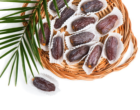 date palm tree: Top view of date fruits medjool in individual packaging paper in a wicker tray with green palm leaf isolated on white background