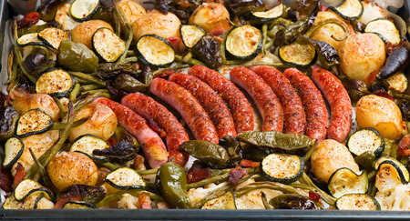 baked: Baked in a oven potatoes with vegetables and sausages on a oven-tray Stock Photo