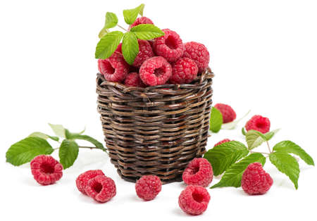Red raspberry with green leaves in a old little basket isolated over white background