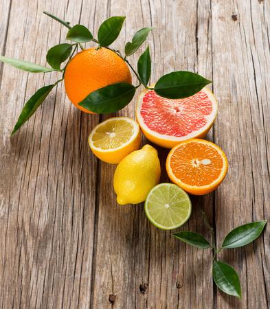 hojas antiguas: Variedad de frutas de colores cítricos (pomelo, naranja, limón, lima) con hojas sobre un fondo de madera vieja. Foto de archivo