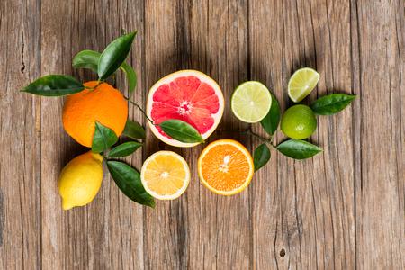 素朴な木製の背景に平面図を柑橘系の果物 (グレープ フルーツ、オレンジ、レモン、ライム) の小枝します。