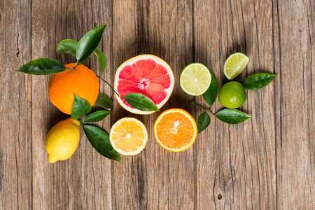 half full: Twig with citrus fruits (grapefruit, orange, lemon, lime), top view on a rustic wooden background.