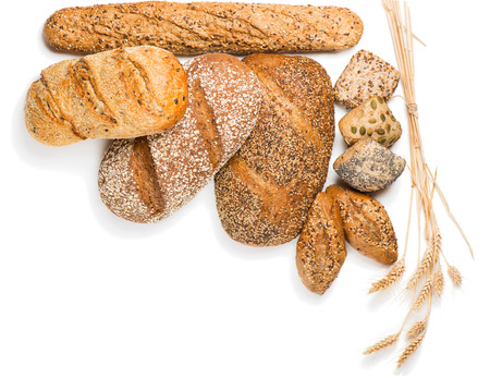 Top view of composition with bread, rolls and wheat ears isolated on white background.