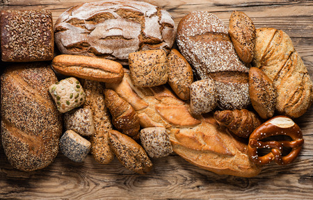 Top view of assortment of different kind of cereal bakery: bread, pasties, buns, pretzel and croissant on old wooden background. Stockfoto