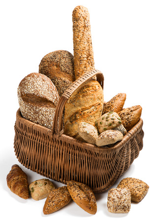 integral: Composition with bread and rolls in wicker basket isolated on white background. Stock Photo