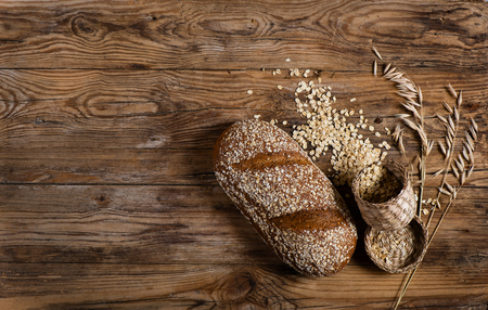 oats: Top view of bread with rolled oats and oat florets on old wooden background with space.